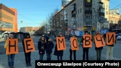 "Activists in Dnipro, Ukraine's fourth-biggest city with about 1 million people, hold single-letter posters on November 24 that spell out, ""Don't be silent,"" to protest violence against women."