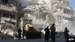 Civilians watch as a tractor clears the rubble following Syrian government air strikes in the rebel-held neighborhood of Tariq a-Bab in Aleppo on September 24.