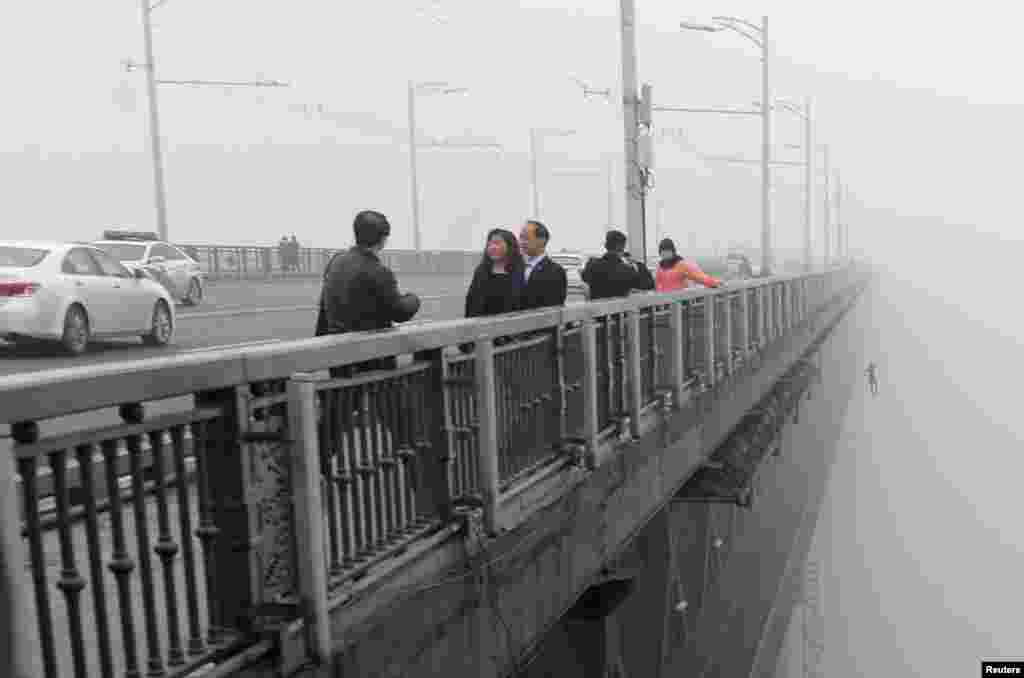 A person can be seen in the distance jumping off the Wuhan Yangtze River Bridge in China's Hubei Province. A young couple jumped into the Yangtze River from the bridge one after another in the haze on February 27. Police said the couple was still missing and is not believed to have survived. (Reuters/China Daily)