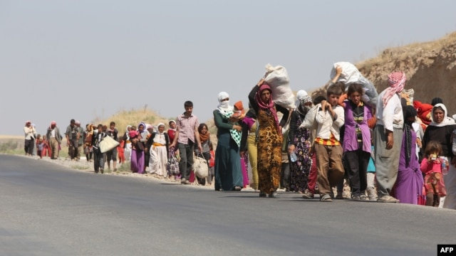 Displaced Iraqi families from the Yazidi community cross the Iraqi-Syrian border at the Fishkhabur crossing, in northern Iraq, on August 13.