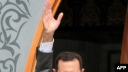 Syrian President Bashar al-Assad salutes a crowd in the town of Al-Raqqa in early November.