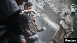 A man in eastern Ghouta is helped after a bombing attack in the Syrian region.