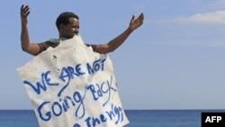 «Ми не повернемось назад» – мігрант тримає плакат на березі моря на Італійсько-Французькому кордоні, червень 2015 року