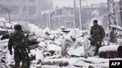 Syrian pro-government forces walk as snow falls in Aleppo on December 21.