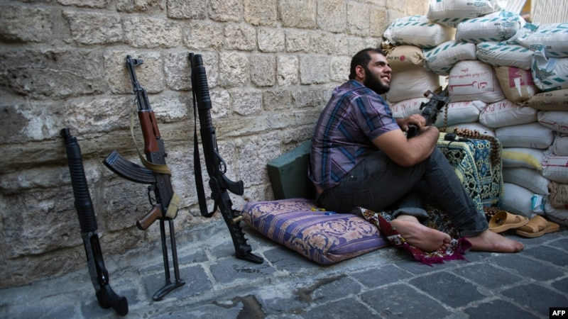 A Syrian rebel fighter mans a checkpoint in the northern city of Aleppo on August 20.