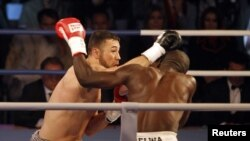 Afghan-German boxer Hamid Rahimi trades punches with his Tanzanian opponent, Said Mbelwa, in their WBO title bout in Kabul on October 30.