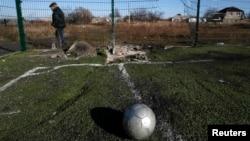 Воронка от взрыва на стадионе около школы в Донецке 6 ноября. Тогда погибли два подростка