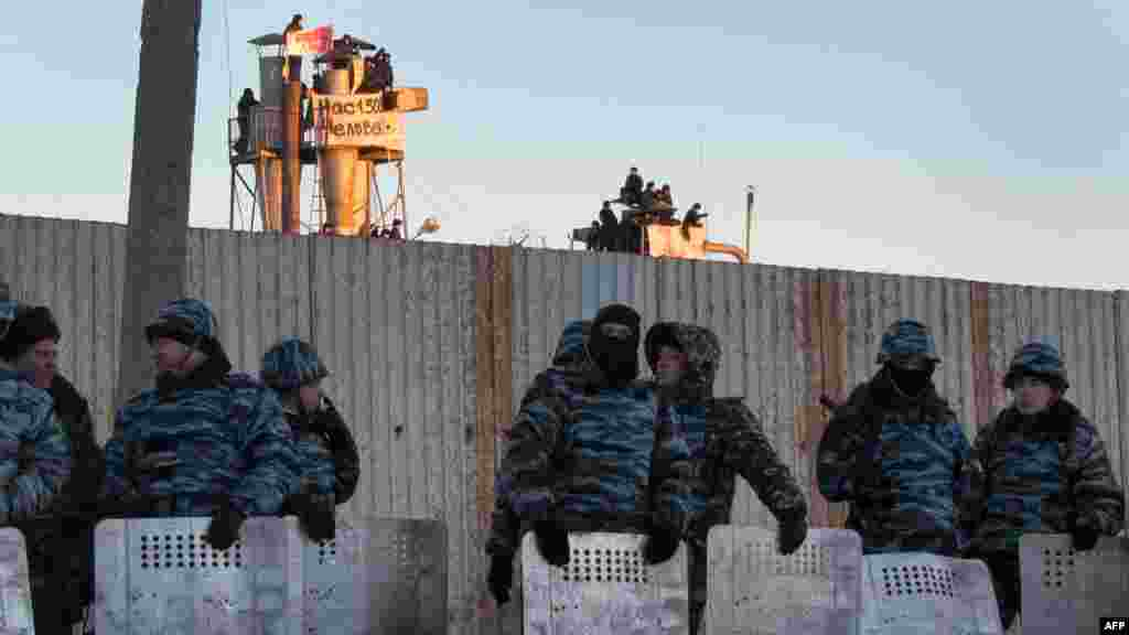 Police officers in riot gear cordon off the prison, with protesting inmates in the background.