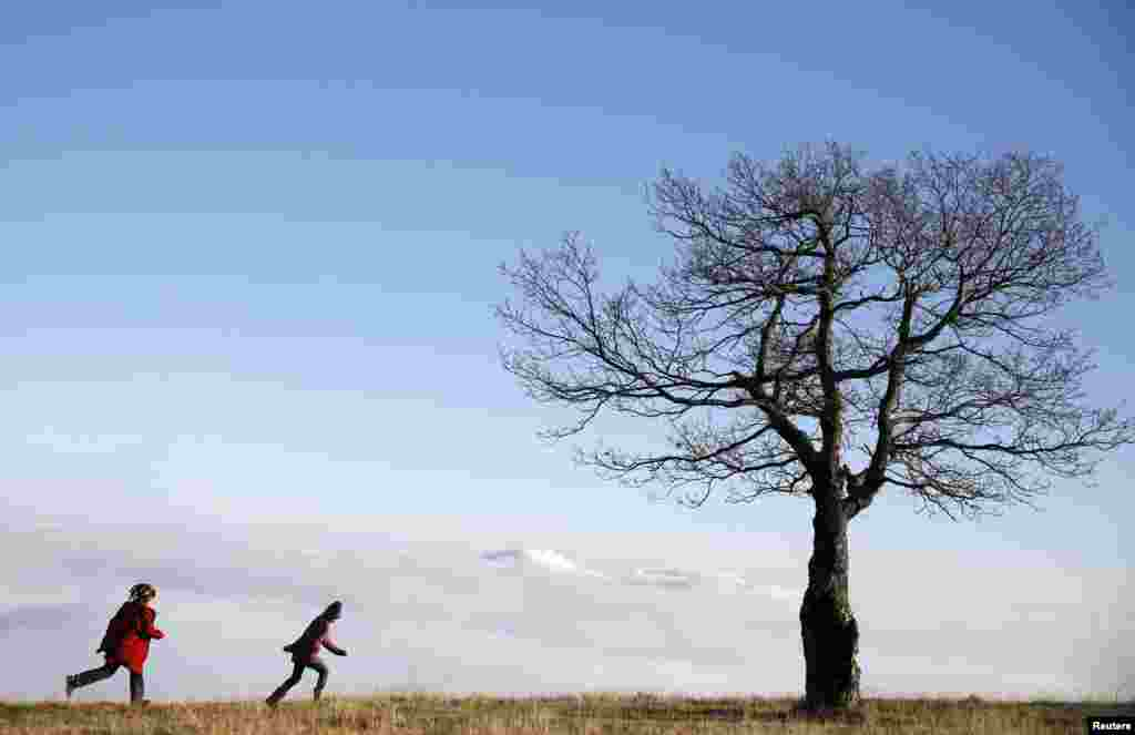 Children run as they play near a tree standing in front of fog over the central Bosnian town of Zenica in the Lisac mountain range.