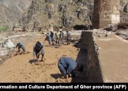 Afghan workers scramble to protect the minaret from floodwaters late last month.