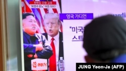 A man watches a television news program showing US President Donald Trump (C) and North Korean leader Kim Jong-Un (L) at a railway station in Seoul on August 9, 2017