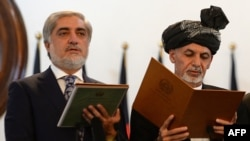 Afghan President Ashraf Ghani (right) administers the oath to Abdullah Abdullah as Afghanistan's newly created post of chief executive in Kabul on September 29.