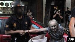 Полиция шеруге шыққан әйелді тұтқындап барады. Испания, 13 шілде 2012 жыл. (Көрнекі сурет).