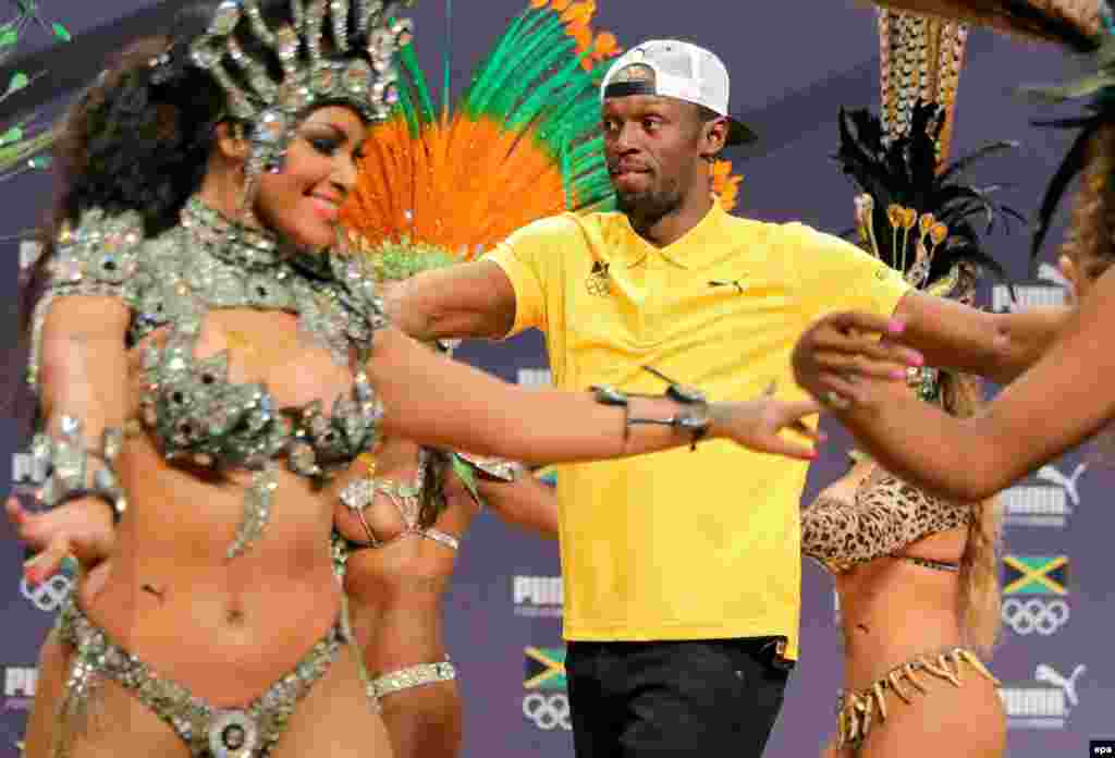 Sprinter Usain Bolt of Jamaica sambas with some dancers during a press conference.