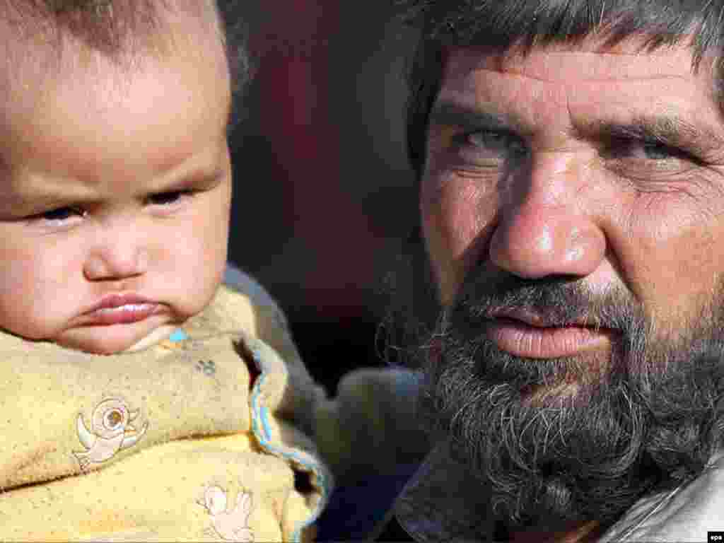 Afghanistan -- An Afghan refugee holds his baby, as he stands outside his temporary shelter at a refugee camp in Kabul, 19Nov2008.