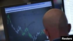 Трейдер наблюдает за котировками акций на своем компьютере. Иллюстративное фото.