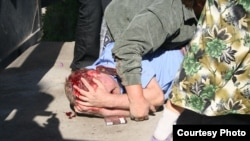 Полицейский, раненный в столкновении с жителями поселка Шанырак близ Алматы. 14 июля 2006 года. Фото журналиста Казиса Тогузбаева.