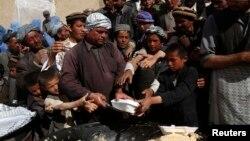 Выжившие после схода оползня в провинции Бадахшан стоят в очереди за едой. 5 мая 2014 года.