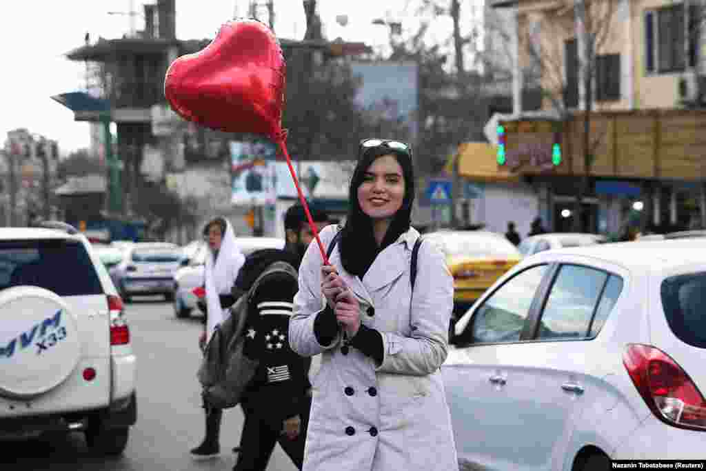 Iran, February 14: A woman poses with a heart-shaped balloon on Valentine's Day in Tehran. Iran confirmed its first two deaths from the coronavirus on February 19 after denying an earlier report that a woman had died from COVID-19 on February 12. The pandemic has killed 1,812 Iranians as of March 23.
