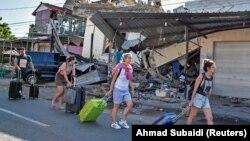 Попри вразливість до землетрусів, індонезійські острови приваблюють туристів. На фото: група мандрівників проходять повз пошкоджені будівлі в місті Пеменанг на Ломбоку, 6 серпня 2018 року