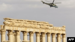 "Syria -- A Russian Mil Mi-24 ""Hind"" attack helicopter flies above the damaged site of the ancient city of Palmyra, March 4, 2017"