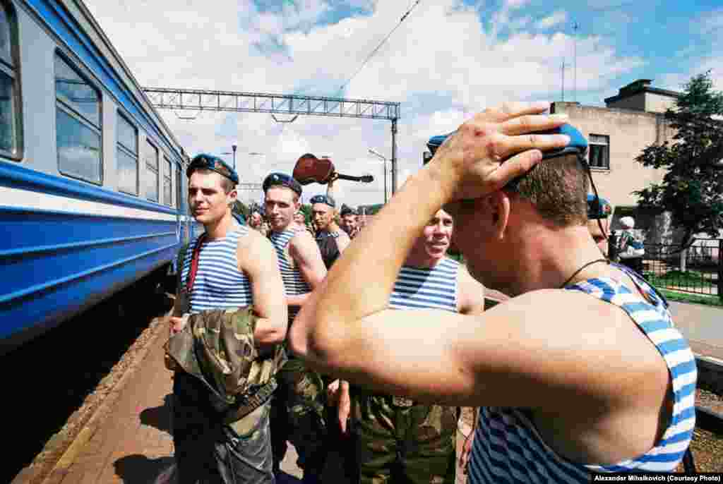 Soldiers wearing the blue beret of the special forces wait for the train home.