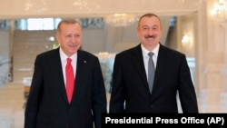 Azerbaijan -- Turkish President Recep Tayyip Erdogan, left, and Azerbaijani President Ilham Aliyev walk before a meeting in Baku, October 14, 2019