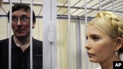 Former Ukrainian Interior Minister Yuriy Lutsenko (left) in a defendant's cage with former Prime Minister Yulia Tymoshenko in a courtroom in Kyiv in May 2011.