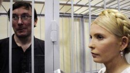 Former Interior Minister Yuriy Lutsenko (left, in defendant's cage) and Yulia Tymoshenko talk in a courtroom in Kyiv in May 2011.
