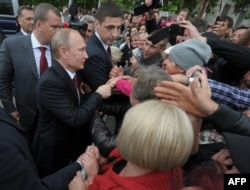 Russian President Vladimir Putin meets local residents during a visit to the Crimean port of Sevastopol on May 9, 2014.