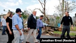 U.S. President Donald Trump walks past hurricane wreckage as he participates in a walking tour in Puerto Rico on October 3.