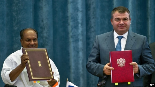 Indian Defense Minister A.K. Antony (left) and his Russian counterpart, Anatoly Serdyukov, pose with documents after agreement signing in New Delhi on October 10.