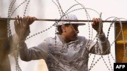 Qahirədə prezident H.Mübarək istefa verən gün aksiya iştirakçısı dövlət televiziyasına gedən yoldan tikanlı məftili təmizləyir, 11 fevral 2011