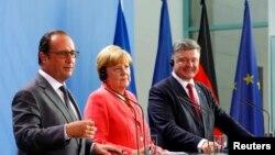 Прэзыдэнт Францыі Франсуа Алянд (зьлева), канцлер Нямеччыны Ангела Мэркель (у цэнтры) і прэзыдэнт Украіны Пятро Парашэнка на сустрэчы ў Бэрліне, 24 жніўня 2015 году