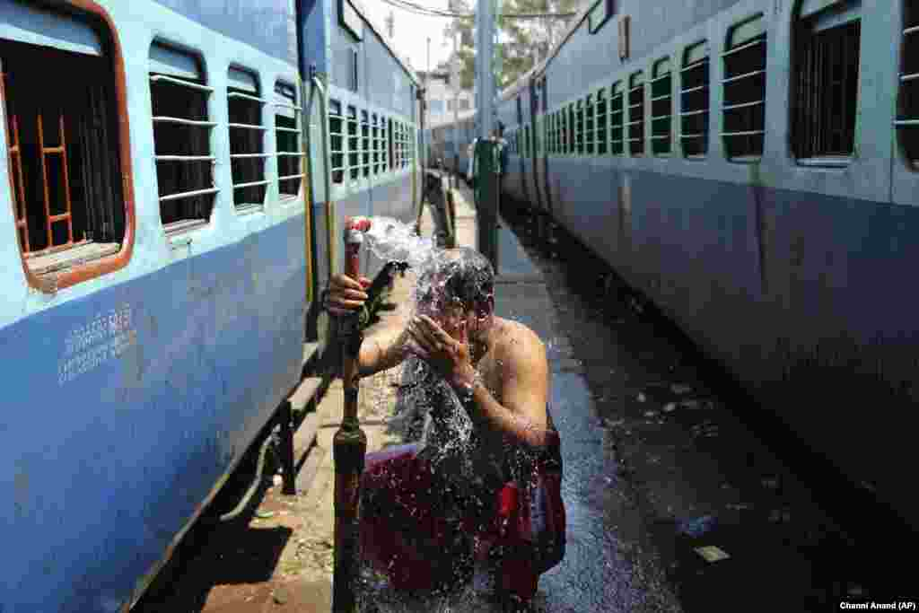 A passenger bathes beside railway tracks on a hot summer afternoon on the outskirts of Jammu, India. Temperatures reached 42.5 Celsius. (AP/Channi Anand)