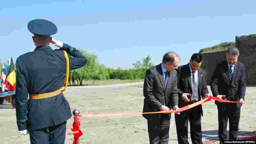 NATO Assistant Secretary-General Gabor Iklody (left) cuts a ribbon at the clearance site with Moldovan Defense Minister Vitalie Marina (center) and Romanian Ambassador Marius Lazurca.