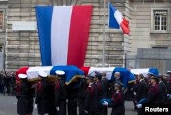 Францускія паліцыянты нясуць труны загінулых калегаў на цырымоніі разьвітаньня ў Парыжы 13 студзеня