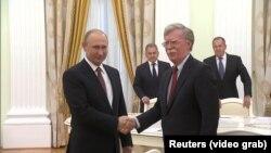 Президент России Владимир Путин (слева) приветствует советника президента США по национальной безопасности Джона Болтона. Москва, 13 июня 2018 года.