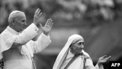 Фатаздымак зроблены 3 лютага 1986 году. Маці Тэрэза і папа Ян Павал II вітаюць прыхажан у Калькуце. Пантыфік наведаў дом, дзе яго сутсрэла Маці Тэрэзы, падчас свайго 10-дзённага дзяржаўнага візыту ў Індыю.