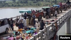 People walk past bodies of some of those killed in a stampede on a bridge near the Ratangarh temple in the Datia district in the central Indian state of Madhya Pradesh on October 13 after rumors of a bridge collapse set off panic.
