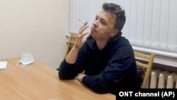 """Raman Pratasevich smokes a cigarette while speaking in a video from a detention center in Minsk, broadcast by the state-controlled ONT channel on June 2. """"I have noticed handcuff marks on his hands,"""" his mother says."""