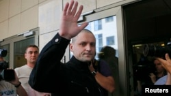 Sergei Udaltsov (center) gestures to supporters and reporters as he enters a court building in Moscow in July 2014.