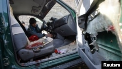A police officer inspects the interior of the car the chief of police of Nimroz Province was in when it was hit by a roadside bomb that killed him.