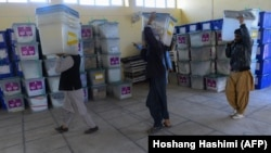 Afghanistan Independent Election Commission workers carry ballot boxes into a warehouse after ballots were counted during the country's legislative election, in Herat on October 21.