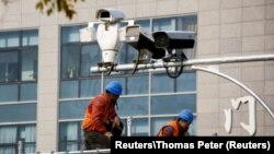 Мужчины работают над установкой камер наблюдения в Пекине.