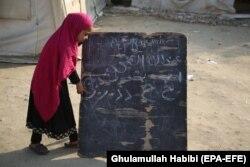 Девочка у школьной доски в афганской провинции Нангархар, февраль 2021 года. Из-за нехватки помещений школьные занятия в Афганистане часто приходится проводить на открытом воздухе