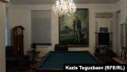 За бильярдным столом в доме Заманбека Нуркадилова — кресло, в подлокотнике которого сохранились следы от двух пуль, прошедших насквозь через его грудную клетку, и портрет, в нижней левой части рамы которого сохранился след от пули, прошедшей насквозь через его голову.