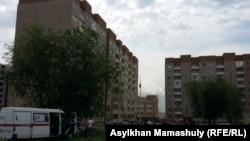 """Апатты жағдайдағы көпқабатты үйдің алдында тұрған адамдар. """"Алғабас"""" ықшам ауданы, Алматы, 2 маусым 2016 жыл (Көрнекі сурет)."""