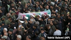 Iranian policemen carry a the coffin of colleague a colleague who was one of three officers killed last month when a bus rammed into them in February.