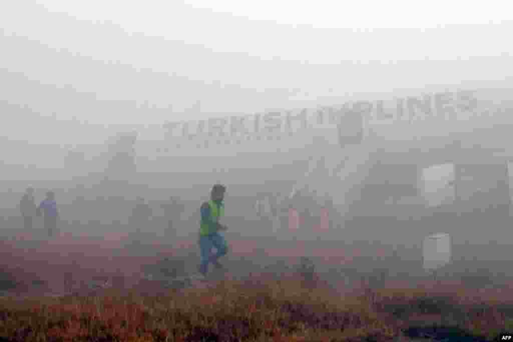 Passengers leave a Turkish Airlines plane that skidded off the runway on landing at Kathmandu airport in Nepal. No one on board was injured, although one witness described how terrified passengers leaped from their seats as the cabin filled with smoke after the plane skidded to a halt. (AFP/Dikesh Malhotra)